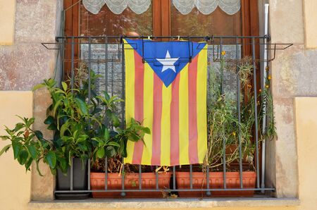 The blue version of the pro-independence Catalan flag is on the metal lattice in the window. It is named the Blue Starred Flag.