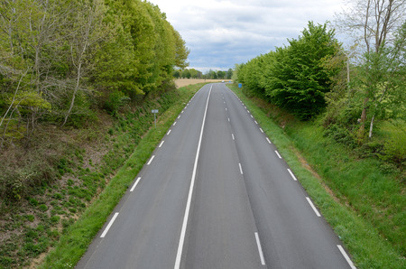 Empty asphalt road is surrounded with green roadside trees and bushes. Stock Photo