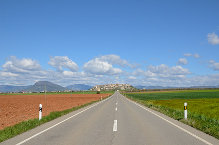 The asphalt road leads to the town surrounded with the fields.