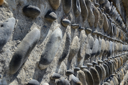 Pebbles inserted in the wall, mortar with the rows of the smooth rounded stones, diminishing perspective