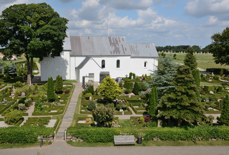 Jelling church with runestones, cemetery and tourists around