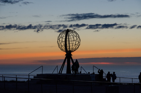 Silhouettes of the globe and people against the midnight sky at the viewpoint of the North Cape Stock Photo