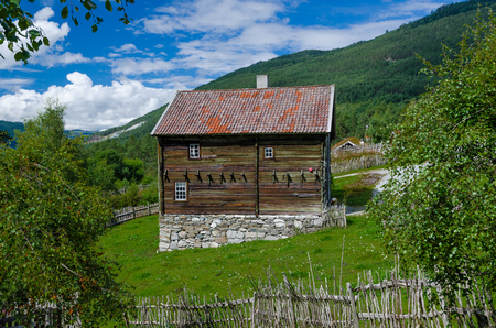 A log farmhouse with tiled roof and stone base in the Norwegian o Banque d'images - 119341137