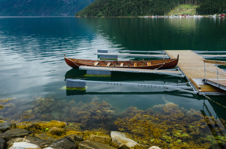 Floating dock with a rowboat mooring in the Norwegian fjord Stock Photo