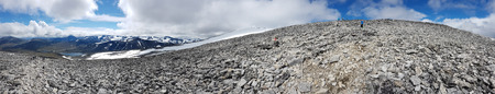Moraine of the mountain Glittertind with a snowfields against other summits far away