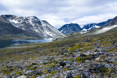 The Nedre Steinbuvatnet lake at the foot of the bare mountains in the Jotunheimen national park