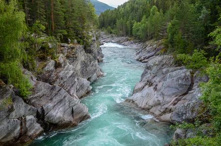 Flacher und schneller Gebirgsfluss Sjoa mit starker Dauerströmung und bewaldeten Steilufern Standard-Bild