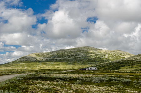 National Tourist Road Rondane across the lichen-covered tundra area with the barren mountains of the Rondane massif.