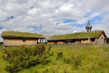 Venabygd ancient wooden church with an eco-roof, a stone fence and a grassy pasture near 版權商用圖片
