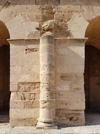 Ancient wall with a column between the arcs in the ancient African colosseum of El Djem Foto de archivo - 130723017