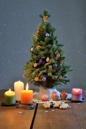Christmas tree surrounded by the candles, cookies, and coloured eggs on the table. Stock Photo