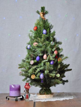 Christmas tree with the candles on the wooden table