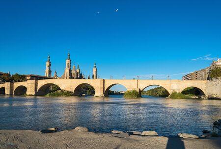 Puente de Piedra bridge across the river Ebro and the ancient church Basilica del Pillar in the Spanish city Zaragoza Stock Photo
