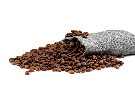 Roasted coffee beans spilling from a burlap sack isolated on white background with bokeh effect Stock Photo