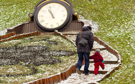 father and son walking in winter park, they climb the stairs, they were in warm winter jackets, its cold outside Stock Photo