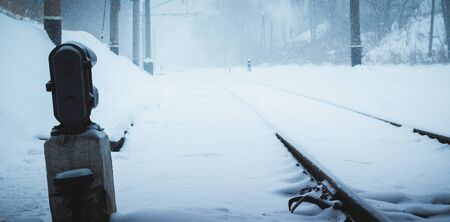 cold winter view of the railroad tracks, a very beautiful snow falls and is the lone traffic light and road goes into the distance