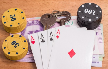 four of a kind: always nice to win, chips for poker and old metal keys Soviet times on a wooden background Stock Photo