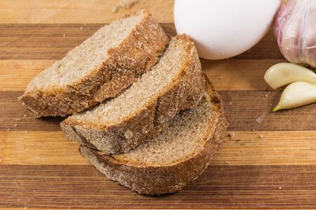 black bread: black bread, egg and garlic on a wooden background, garlic is useful against colds and egg contains protein
