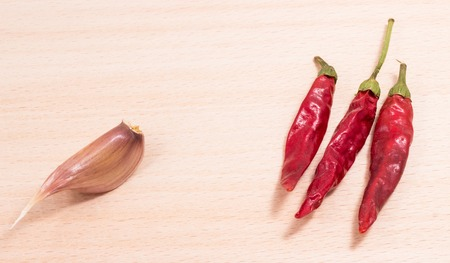 heart very: red pepper and garlic on a wooden background, this sharp vegetables taste and very helpful, garlic for the prevention of colds and peppers good for the heart