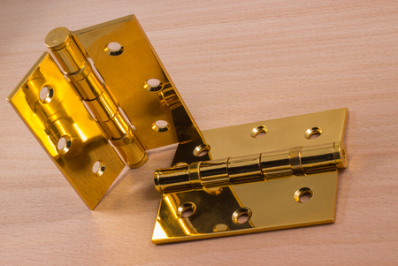 hinges on a wooden background, gold color metal