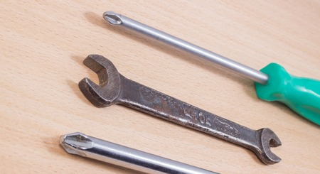 disassemble: screwdriver on a wooden background, it is a tool for screwing and unscrewing screws