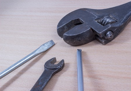 unscrewing: screwdriver on a wooden background, it is a tool for screwing and unscrewing screws
