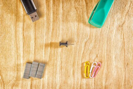 Office accessories on a wooden background, stapler, paper clips and a flash drive for storing information