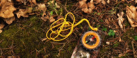 A compass on the ground in the forest is a device for a landmark. It shows the direction, its arrow always points north, around dry leaves, moss and plants Stock Photo