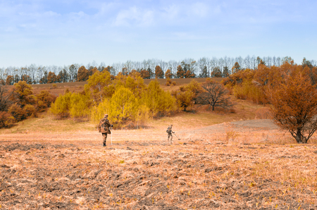 under ground: Bright autumn colors under the blue sky, two young travelers in nature, one checks the ground with a metal detector and the other observes