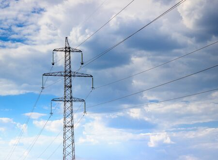 against the current: Nicely stretched wires against the blue sky on them goes current high voltage dangerous for life Stock Photo