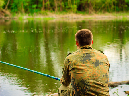 The fisherman sits by the river holding the rod he watches the float that carries away the current