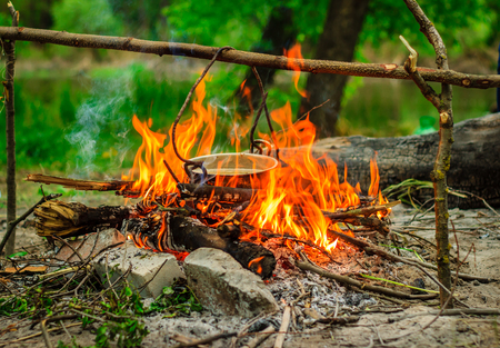 Cook on the nature is not only delicious but also very brightly lit the fire around the metal boiler is going smoke Stock Photo