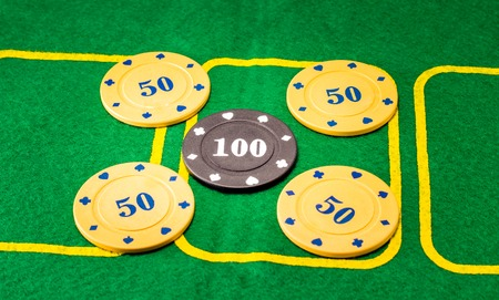 Background of five plastic chips for poker, one is different one which in the middle it is more expensive and meaningful than the rest