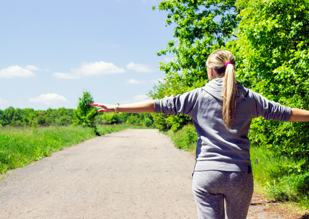 Young woman with blond hair in sports clothes is walking along the road with arms outstretched enjoying a walk on the beautiful nature under a blue sky with clouds 免版税图像