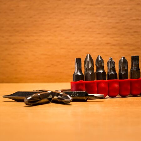 Screwdriver bits in a red case on a wooden background Stock Photo