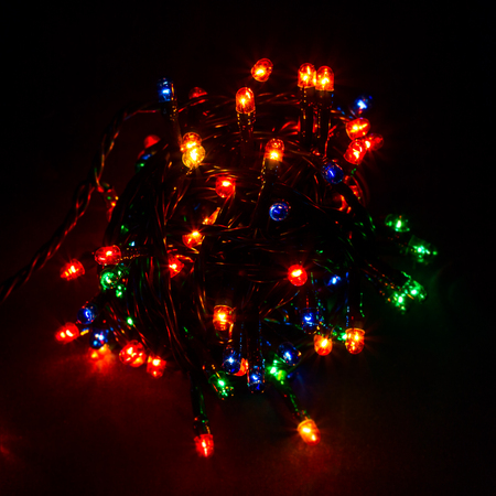 Glowing ball festive garland on a dark background bright and positive red green blue