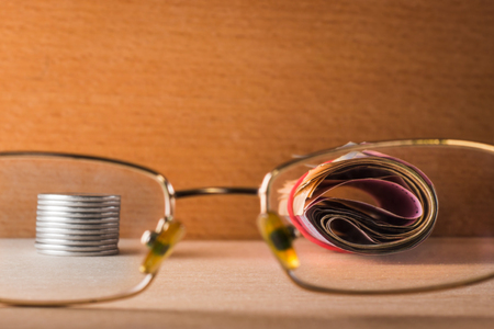 bundle of paper money and metal coins look through the transparent glasses of eye glasses on a wooden background Stock Photo