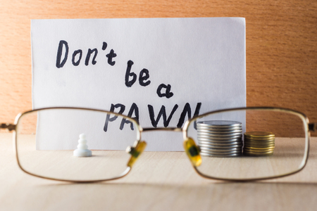 english letters: Do not be a pawn inscription in English near a pawn and coins on a wooden background Stock Photo