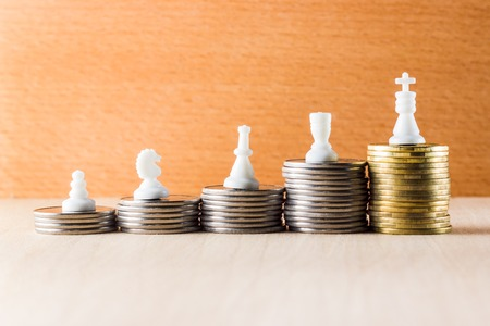 Career ladder of coins and chess pieces symbolizing different work positions