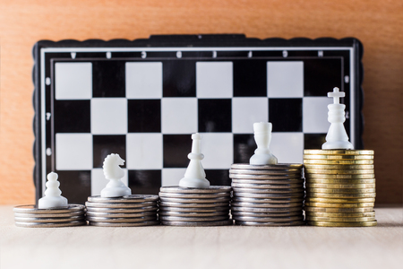 Career ladder of coins and chess pieces on the background of a chessboard