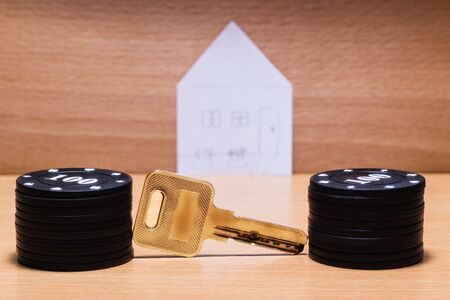 metal key and chips for playing poker on the background of a paper house Stock Photo