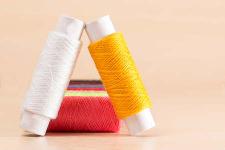 two coils of thread stand leaning against each other concept of sewing Stock Photo