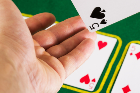 hand of the player throws a card on the table for poker The concept of the casino is a popular board game all over the world