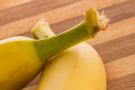 green tails of bright yellow bananas on a wooden background healthy fruits