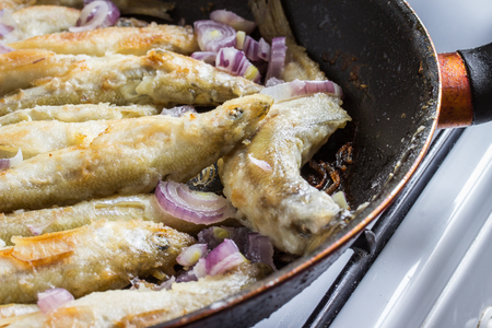 fried smelt fish lies on the frying pan looks very appetizing Stock Photo