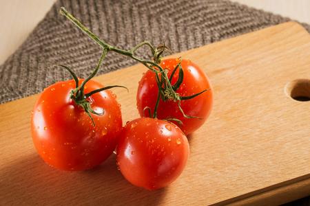 きれいな明るいトマトは、彼らは新鮮で熟した水の滴で覆われている木製のボードの上に横たわっています 写真素材