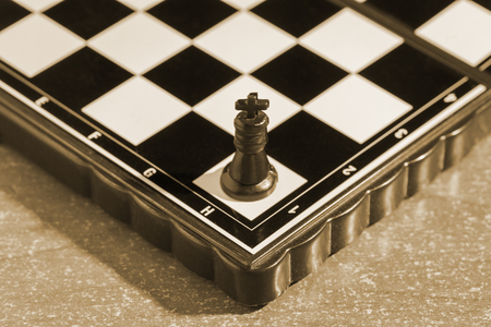 black king on a chessboard alone is the main figure in a very popular board game