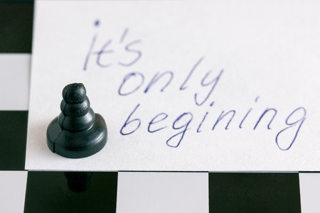 black pawn on a chessboard and an inscription in English it is only beginning Reklamní fotografie