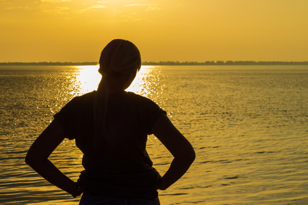girl looks like the sun sets over the estuary brightly lit by the water with a warm glow