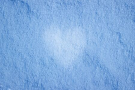 texture of snow in the evening with a heart in the middle of a symbol of love cold season
